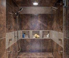 The luxurious outdoor shower features a mix of stone pavers and mulch for  proper drainage