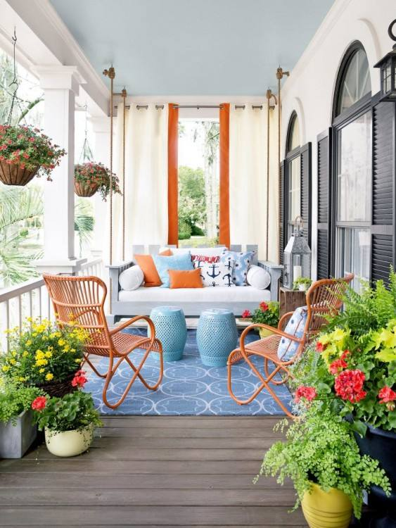 Blue bench, patio table and chairs by a wall in an English cottage garden,  summertime