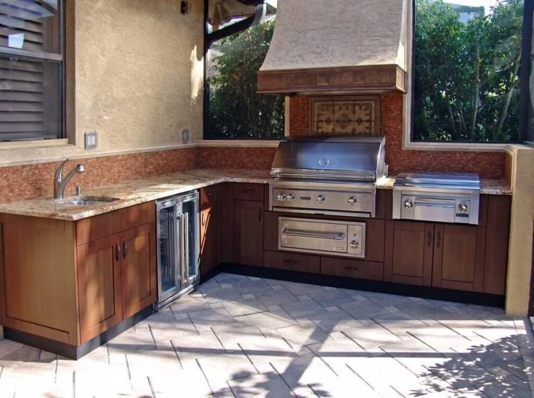 Designed with natural stone to complement the natural wood ceiling,  this outdoor kitchen design was