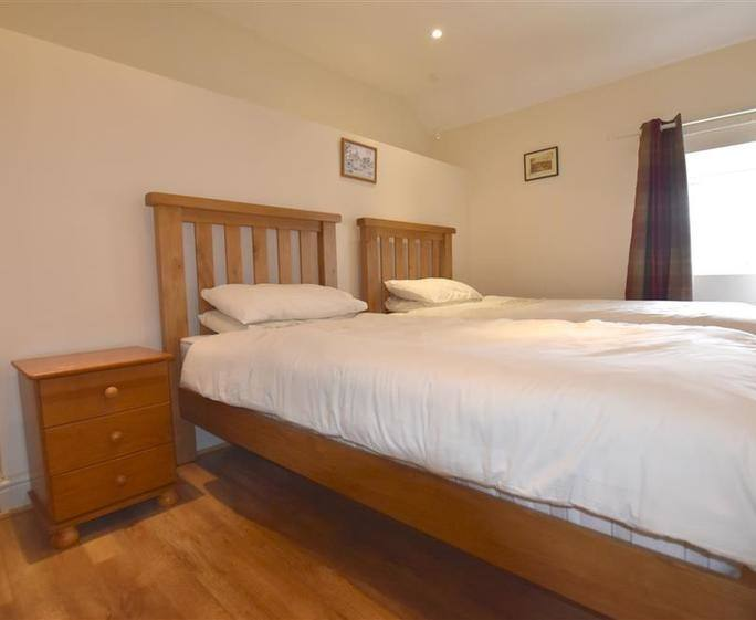 Rooks' Retreat Ground floor bedroom with bed, wardrobe, chest of drawers,  double doors to patio
