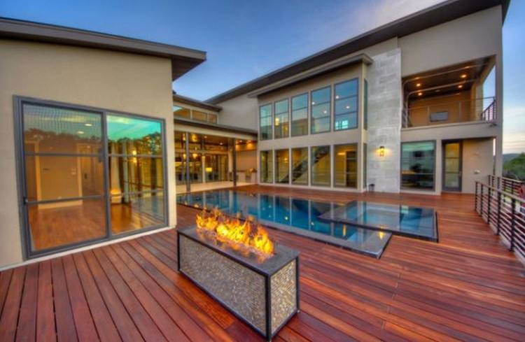 The fireplace's distressed red bricks stand in beautiful contrast to the  pool's smooth gray surface and also give the patio