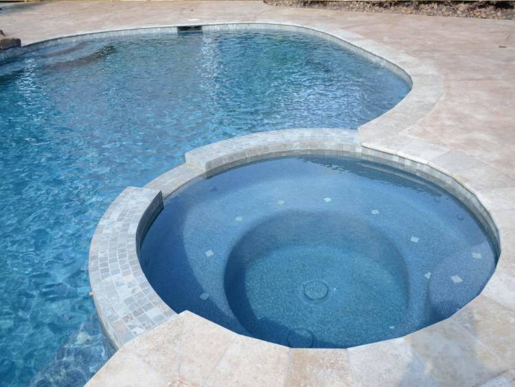new pool design includes water features walk in sun shelf marble deck spa  and custom rock