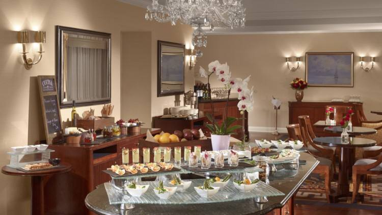 A buffet overlooks dining tables with chairs and sofas