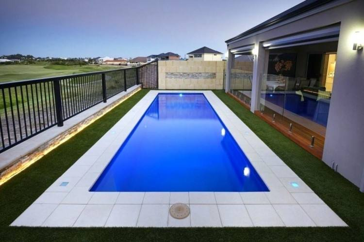 Just off the main living level is a covered entertaining space, sheltered  by the white volume of the level above it, as well as a pool and lounge  deck that