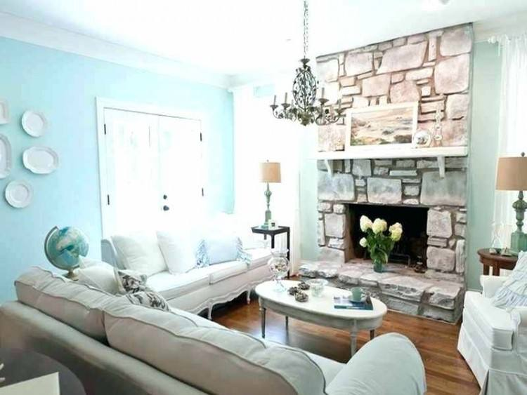 Driftwood over the mantel and as the base of a table add to the modern  coastal look of this open floor plan living space